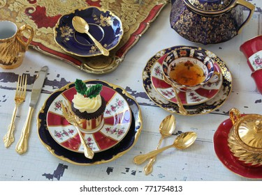 Christmas high tea party - vintage bone china red and dark blue teacups, teapot, gold cutlery flatware on a distressed wood table