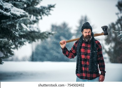 Christmas hipster lumberjack with ax in wood.. Wanderlust, hiking and travel. Winter holiday and celebration. New year man in snowy cold forest. Man with beard in winter forest with snow hold axe.