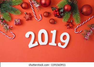 Christmas holiday background with 2019 new year, decorations and ornaments on red table. Top view from above. Flat lay