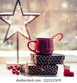 Christmas holiday background with coffee cup with christmas decorations against window