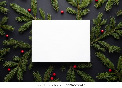 Christmas holiday background with copy space for text. Flat lay, top view. Decorative frame of fir branches and holly berries. Paper notice sheet