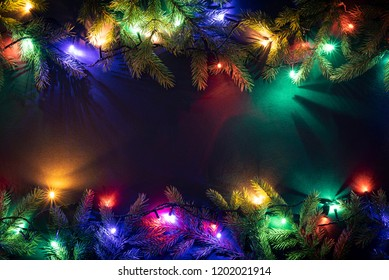 Christmas holiday background with copy space for text. New Year concept. Glowing fairy lights and decor of fir branches. Flat lay, top view