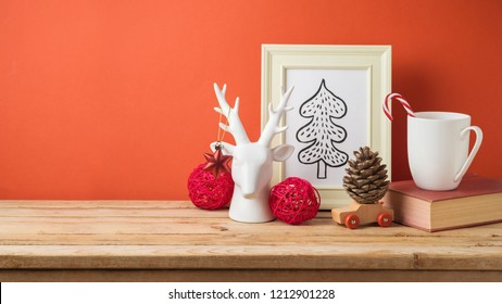 Christmas holiday background with cup, book, drawing and decorations on wooden table