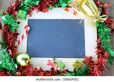 Christmas holiday background and Christmas decorations with blank chalkboard frame for copy space.