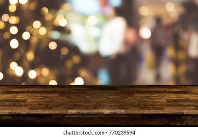 Christmas holiday background with empty dark wooden table top over festive bokeh light decorate on tree. For create montage product display.