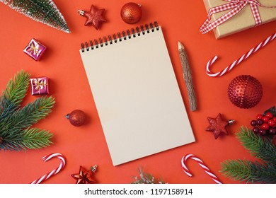 Christmas holiday background with notebook and decorations on red table. Top view from above