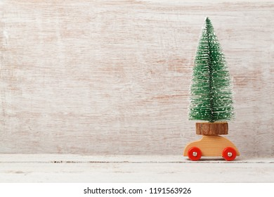 Christmas holiday background with pine tree on toy car on wooden table