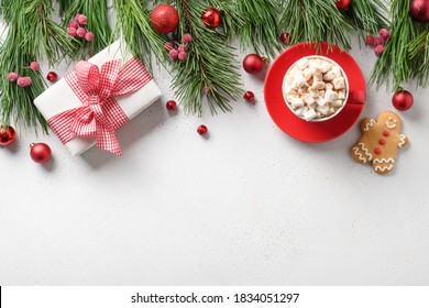 Christmas holiday border with gift, coffee, gingerbread, evergreen branches on white background. Xmas holiday greeting card with copy space. Top view, flat lay.