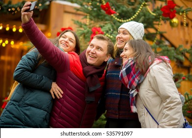 Christmas holiday. Cheerful company of young people makes selfie at Christmas fair. At the foursome excellent mood. All smile. Against the background of beautifully decorated Christmas tree.