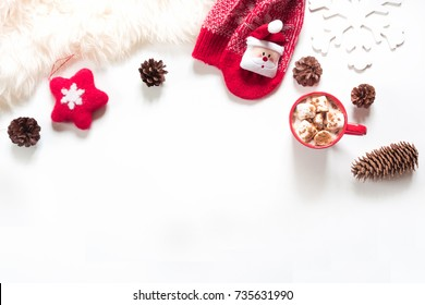 Christmas holiday composition. Hot chocolate with marshmallow, cone, white fur, red felt star, knitted socks on white background. Winter, christmas concept. Flat lay, top view.
