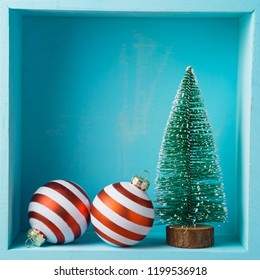 Christmas holiday composition with pine tree and bauble decorations on wooden shelf