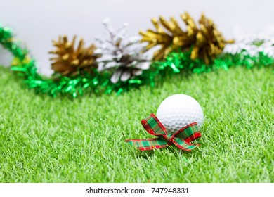 christmas holiday concept for golfer with golf ball and christmas ornament decoration on green grass