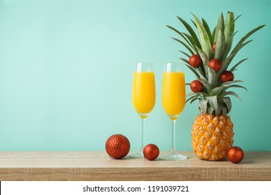 Christmas holiday concept with  pineapple as alternative Christmas tree and juice in champagne glass on wooden table with copy space