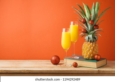 Christmas holiday concept with  pineapple as alternative Christmas tree and juice in champagne glass on wooden table over red background