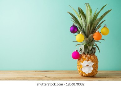 Christmas holiday concept with  pineapple as alternative Christmas tree on wooden table with copy space