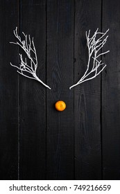 Christmas Holiday Concept - Reindeer Face made of Tangerine and Winter Tree Branches. Minimal Holiday Concept. Flat Lay.