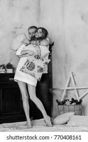 Christmas holiday concept: Young married couple at home in pastel Provence interior. happy couple in white room with Christmas decorations.