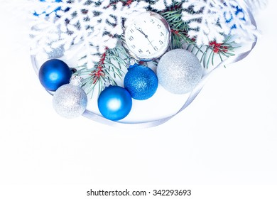 Christmas holiday decoration. Blue, white ornament bauble with brunch of fir or pine, ribbon and old retro clock background. Festive merry xmas, new year celebration. Golden shiny  ball.
