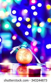 Christmas holiday decoration. Orange ornament bauble with dark black bokeh background. Festive merry xmas, new year celebration. Golden shiny light decorative closeup ball.