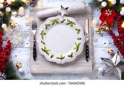 Christmas holiday dinner background; empty dish, cutlery and Christmas tree decoration