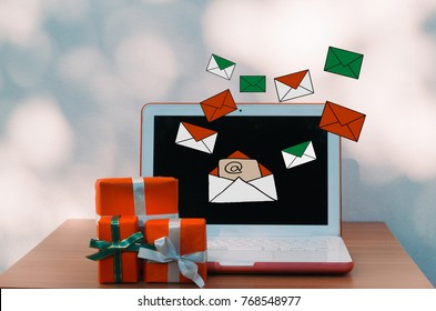 Christmas Holiday and E-mail Marketing concept- new year, presents box and laptop computer with E-mails on wooden table over bokeh wall background and copy text space for writing messages