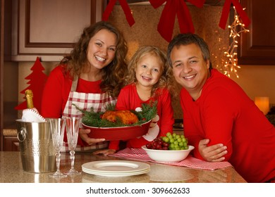 Christmas Holiday Family portrait. Happy family of three preparing Thanksgiving dinner, with turkey and champagne at home. New Year Eve.