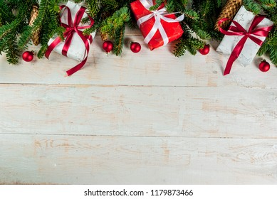 Christmas holiday festive background with pine cones, xmas tree branches, gifts boxes and decorations top view copy space