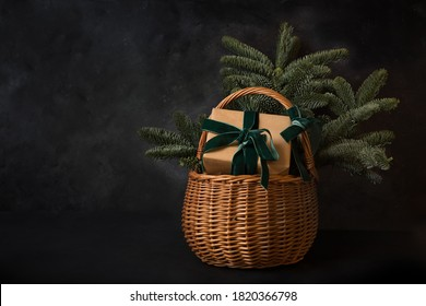 Christmas holiday gift hamper with craft gift and evergreen spice branches on black background. Xmas greeting card with copy space.