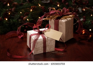 Christmas or Holiday gifts wrapped in traditional paper and ribons, placed on a dark wood surface, and in front of an evergreen holiday decor.