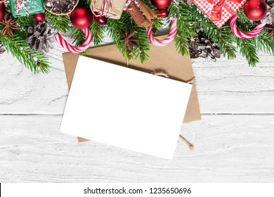 Christmas holiday greeting card with fir tree, gift boxes, decorations, berries and pine cones on white wooden background with copy space for your text. top view. mock up