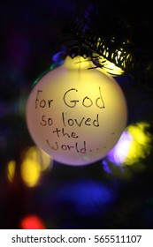 Christmas Holiday Ornament Hanging On Tree Branch Isolated With Lights In Background Bible Verse John 3