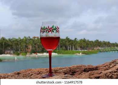 Christmas holiday poinsettia themed crystal goblet stemware in foreground on cloudy day holds red wine with palm trees and lake and beach in background.