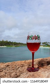 Christmas holiday poinsettia themed crystal goblet stemware in foreground holds red wine with palm trees and lake and beach in background.