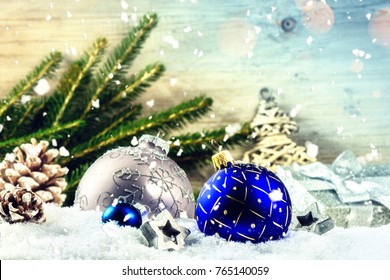 Christmas holiday setting with blue baubles and pine cones over snow. Christmas background with copy space
