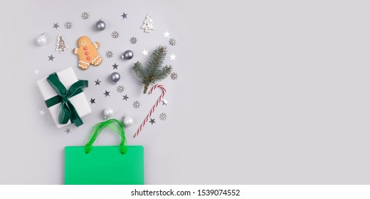 Christmas holiday shopping concept. Green bag with festive gifts, candy cane, treats, decor, glitter confetti on grey background. View from above, flat lay, copy space, banner