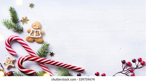 Christmas holiday sweets and fir tree branch on white background. Christmas gift composition.  Flat lay, top view.