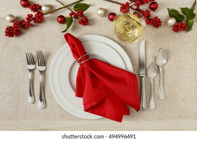 Christmas holiday table setting fine dining home decorations with plate, silverware and wine in wine glass
