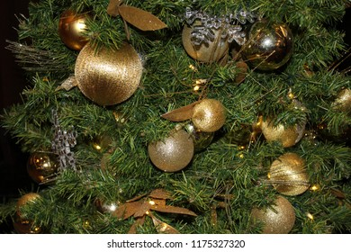 Christmas holiday tree close up decorated with shades of gold ornaments and ribbons and baubles on its green branches
