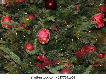 Christmas holiday tree close up decorated with red sparkling ornaments shaped like apples, red holly twigs with berries, round red ornaments, and white tiny lights on its dark green branches