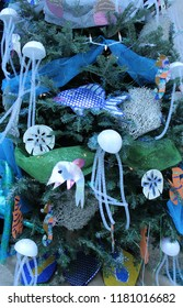 Christmas holiday tree close up decorated with a blue theme of sea creatures including glittery fish, jellyfish, with sparkly blue and green netting as garland plus kirigami crafts on green branches