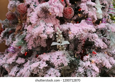 Christmas holiday tree close up decorated with a pink theme of green branches covered with pink foamy coating, red sparkly ornaments, silver bells, and white berries