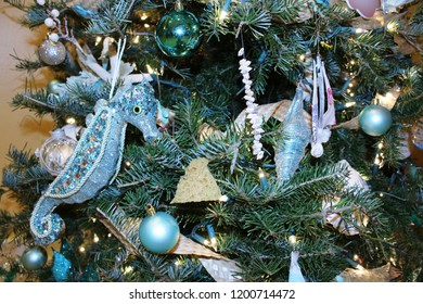 Christmas holiday tree close up decorated with an ocean theme of glittery seahorses, strings of white seashells, round blue ornaments on green branches