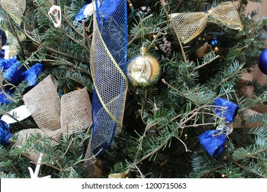 Christmas holiday tree close up decorated with a blue theme of sparkly blue and slivery netting, round silver ornaments, and blue and gold bows green branches
