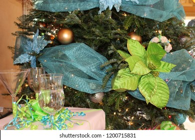 Christmas holiday tree close up decorated with blue netting, gold balls, and green leaves, and with crystal goblets and stemware on nearby table.
