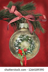 Christmas holiday wreath in gold ornament hanging from pine tree branch