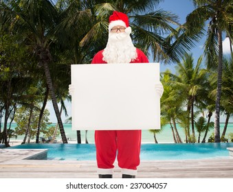 christmas, holidays, advertisement, travel and people concept - man in costume of santa claus holding white blank billboard over swimming pool on tropical beach background