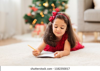 christmas, holidays and childhood concept - smiling girl writing wish list or letter to santa at home