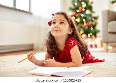 christmas, holidays and childhood concept - smiling girl making wish list or letter to santa at home