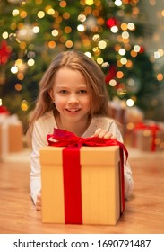 christmas, holidays and childhood concept - smiling girl with gift box at home