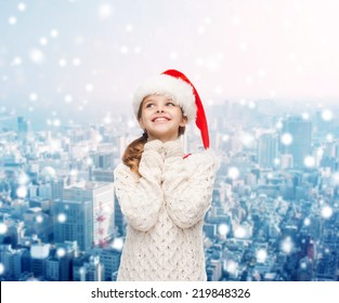 christmas, holidays, childhood and people concept - smiling girl in santa helper hat over snowy city background